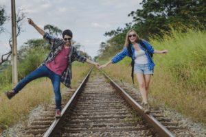 couple-holding-balance-on-train-tracks_23-2147637685
